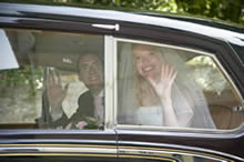 Bride and groom waving from car